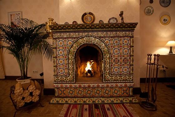 Ресторан Гармошка - фотография 15 - Действующий камин, обрамленный изразцами ручной работы в стиле костромской росписи XIX века.